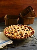 A whole berry pie with a lattice crust on a cooling rack