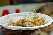 A hand holding paneer kebabs (Indian street food)