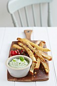 Homemade breadsticks with a basil pesto dip and cherry tomatoes