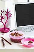 Muesli in a pink spotted Tupperware box next to a laptop