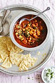 Chicken and chickpea curry with spinach and pepper served with poppadoms and mint raita