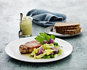 Pork chop with a mixed leaf salad served with wholemeal bread