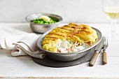 Whiting and salmon pie with a mashed potato topping served with peas