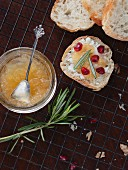Homemade pear jam on a slice of bread with rosemary and pomegranate seeds