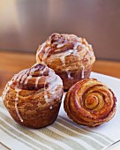 Three cinnamon buns with icing sugar on a napkin