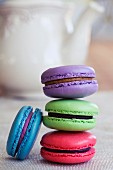 Various different coloured macaroons stacked in front of a teapot