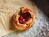 A Danish pastry with cherries on a piece of baking paper, broken