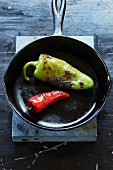 Two charred jalapeño peppers in a cast-iron pan