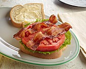 An open BLT sandwich with mayonnaise