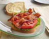 An open BLT sandwich with mayonnaise