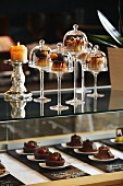 Desserts under mini glass cloches on a bar in a restaurant