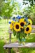 Sommerstrauss aus Sonnenblumen & blauem Rittersporn auf Bank im Freien