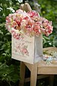 Aufgeblühte zweifarbige Tulpen in romantischer Tasche mit Blütenmotiv