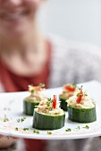 Woman Placing Platter of Cucumber Appetizers on Table