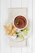 Tomato hummus with tortilla chips and lime wedges (seen from above)