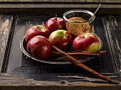 Red apples, cinnamon sticks and brown sugar on a metal plate