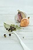 Lorbeerblatt, Pfefferkörner und Piment auf Löffel, dahinter Knoblauchknolle und Zwiebel