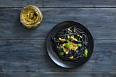 Black squid ink pasta with basil pesto and fresh basil leaves