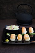 Salmon sushi with wasabi and a cucumber salad