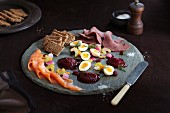 Scandinavian appetiser platter with smoked salmon, beetroot purée, rye bread, boiled eggs and cold beef slices