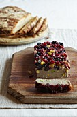 Pâté with cranberries, raisins and sultanas with sliced bread in the background