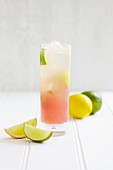 A highball glass of pink lemonade with lemons and limes