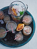 Glasses and a jug of quince lemonade on a wooden tray