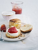 Scones with jam on a porcelain plate with a spoon