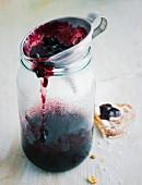 Blackberry jam in a funnel over a jar