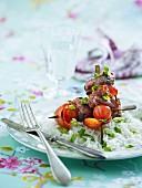 Pork marinated with pesto wrapped in Serrano ham with tomatoes and peppers on skewers served with rice and spring onions