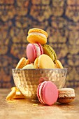 Colourful macaroons, some in a metal bowl