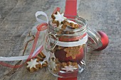 Cinnamon stars in a jar in front of Christmas tree baubles and a ribbon