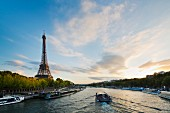 An imposing view of the River Seine with the Eiffel Tower on the left and a sunset to the right