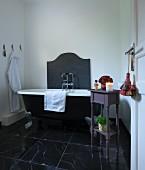 Wanne mit Klauenfüssen und Tischchen als Ablage im Badezimmer mit schwarzem Marmorboden