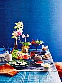 Koreanisches Buffet mit Teekanne, grosser Salatplatte und Kimbap