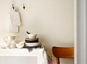 White wooden chopping boards hanging on white wall above stacked crockery and white jugs