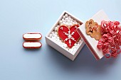 Red and white Christmas biscuits and a Christmas heart in a gift box
