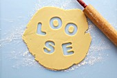 Rolled biscuit dough with the word LOOSE cut out of it
