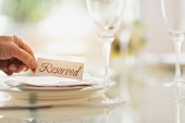 A man placing a reserved sign at a place on a table in a restaurant