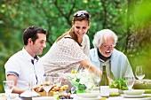 Drei Menschen auf einer Gartenparty