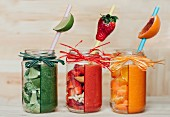 Three different smoothies (red, green and orange) with fruit and vegetables
