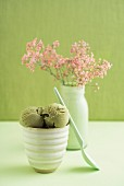 Green tea ice cream in a tub with a vase of gypsophila