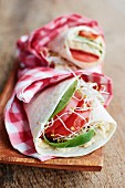 Tortilla wraps with humus, spinach, bean sprouts and tomato slices on a wooden board