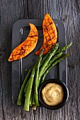 Cooked green asparagus and grilled sweet potato with a dip