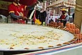 Indischer Mann beim Zubereiten von traditionellem Kulfi