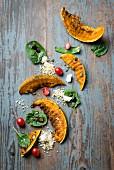 Gegrillte Kürbisspalten mit Bulgur-Spinatsalat und Feta auf Holzuntergrund