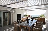 Rattanstühle um Holztisch auf mit Sonnenschutzlamellen überdachter Terrasse