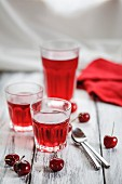 Three glasses of cherry jelly, fresh cherries and tea spoons on a wooden surface