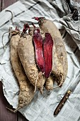 Long beetroots, whole and halved, on newspaper