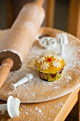 Cupcakes with marzipan fondant surrounded by baking utensils